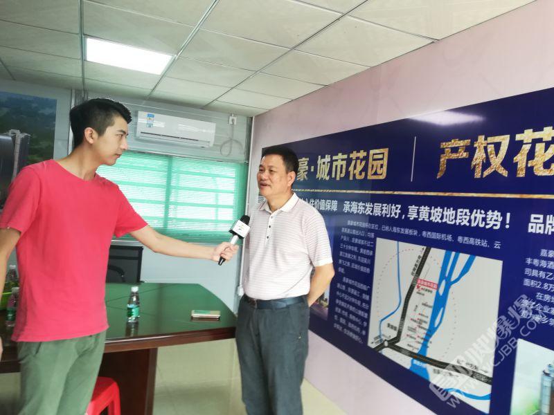吴川黄坡嘉豪城市花园老总黄志明在展览厅向参观团成员介绍了这个小区的规划情况.jpg